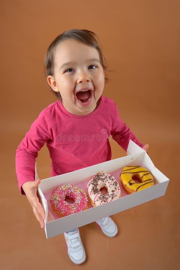 Liten flicka med olika typer av donuts royaltyfri bild