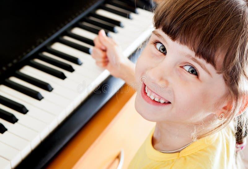 Liten flicka med pianot royaltyfria foton