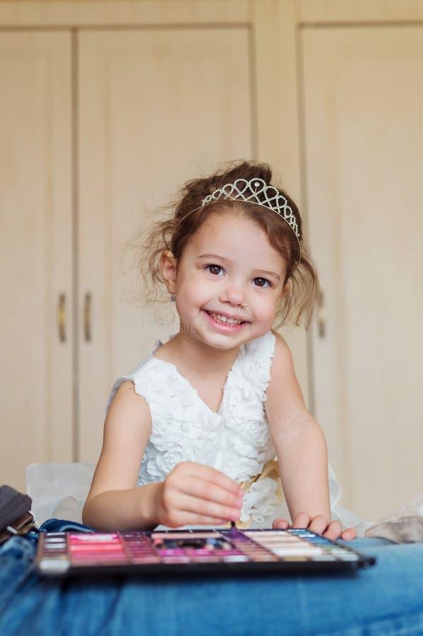 Liten flicka med prinsessakronan som spelar med smink royaltyfri bild