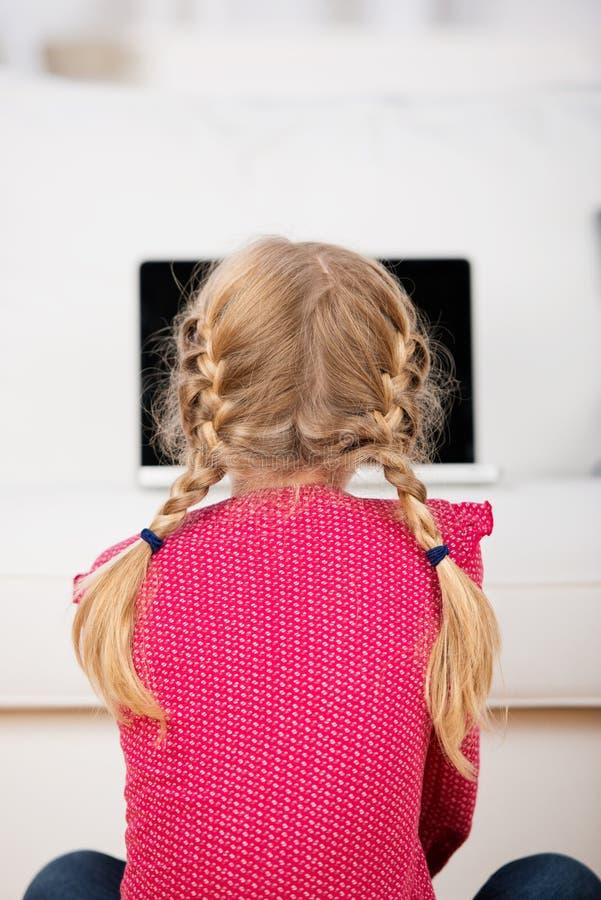 Liten flicka med råttsvansar som ser bärbara datorn royaltyfria bilder