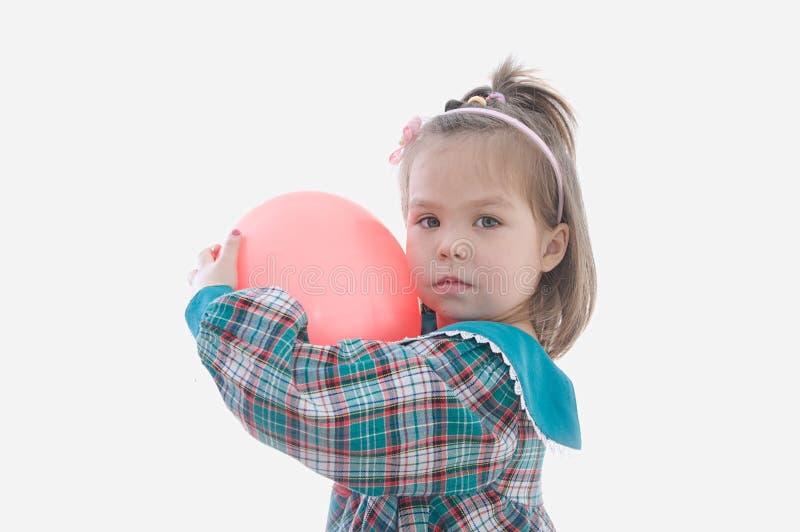 Liten flicka med röd baloon som isoleras på vit bakgrund royaltyfri foto