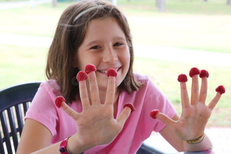 Liten flicka med röda hallon på fingerhänder arkivbilder