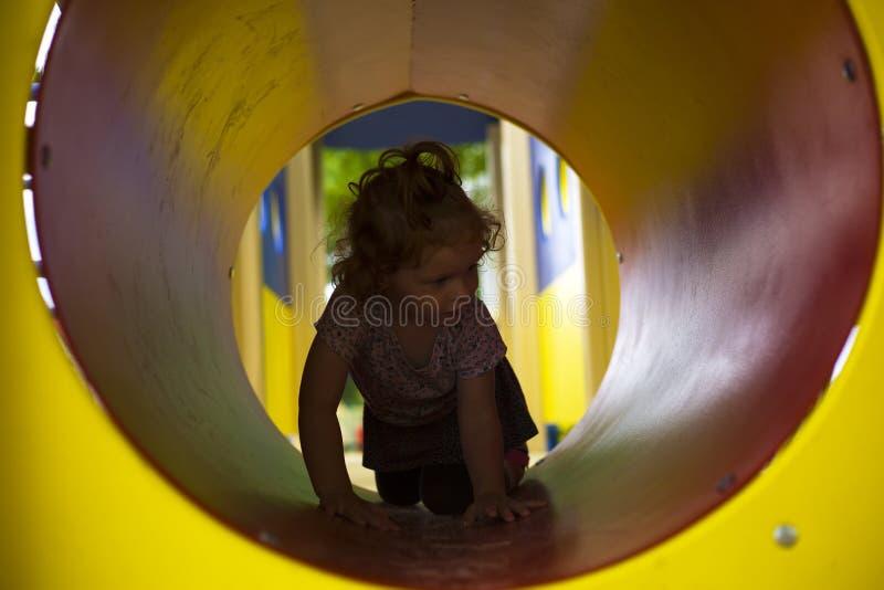 Liten flicka med rött hår som kryper till och med en tunnel i lekplatsen royaltyfri foto