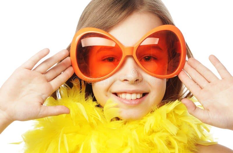 liten flicka med roliga orange carnaval exponeringsglas arkivbild