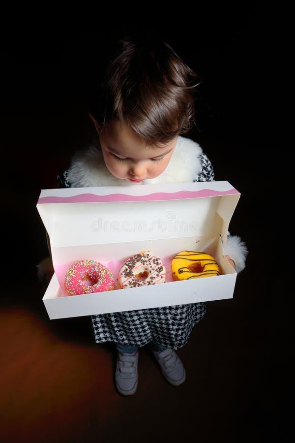 Liten flicka med söta olika donuts fotografering för bildbyråer