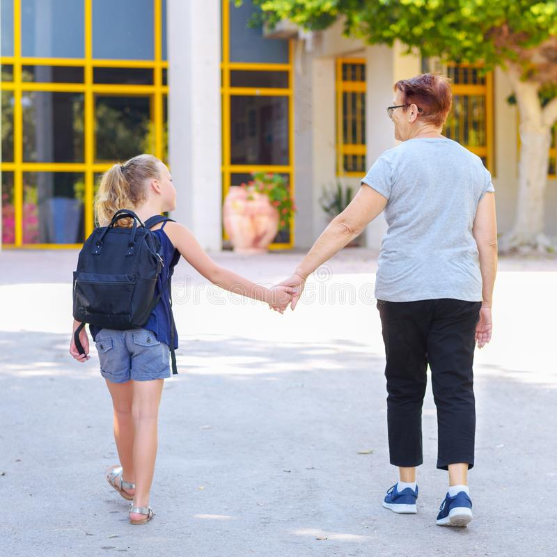 Liten flicka med skolapåsen eller axelväska som går till skola med farmodern tillbaka sikt arkivbild