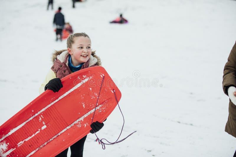 Liten flicka med släden i snön royaltyfri bild