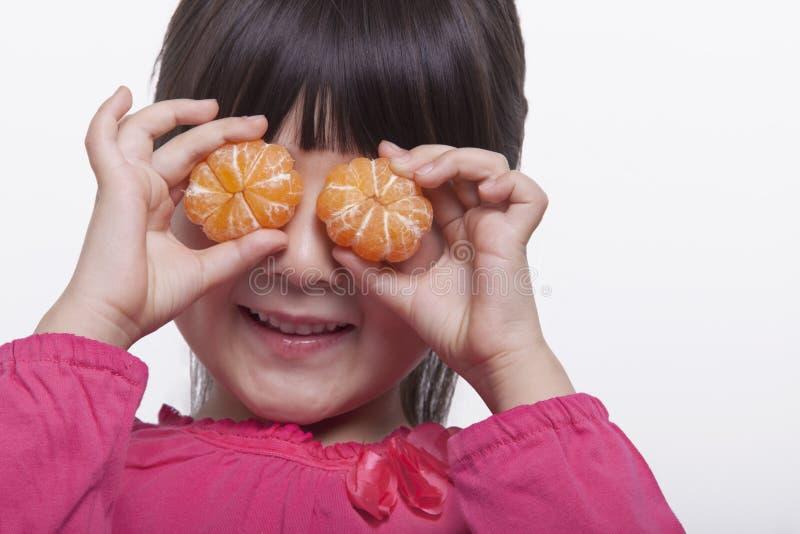 Liten flicka med smällar som rymmer mandariner främsta av hennes head och skuldrastudioskott för ögon, arkivbild