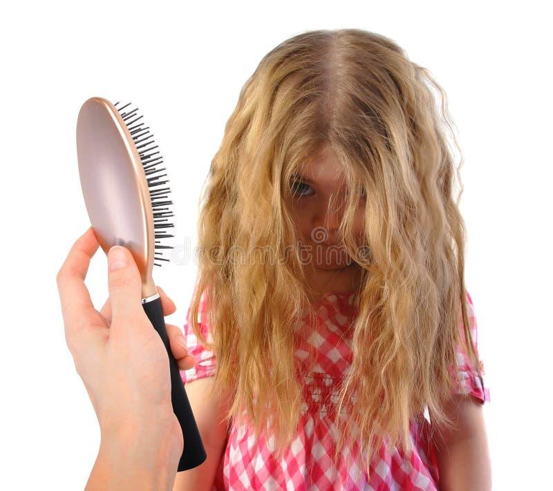Liten flicka med smutsigt tilltrasslat hår på vit royaltyfri foto