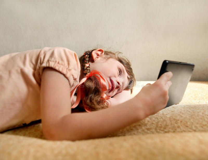 Liten flicka med tableten arkivbild