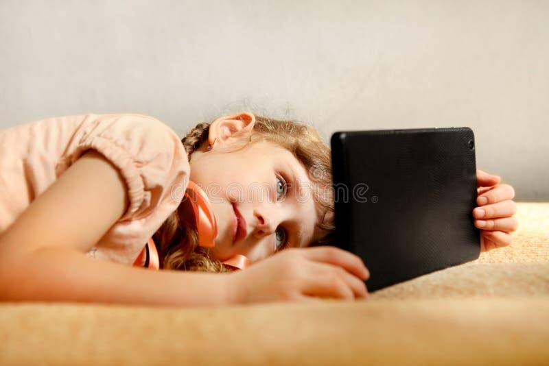 Liten flicka med tableten royaltyfri bild