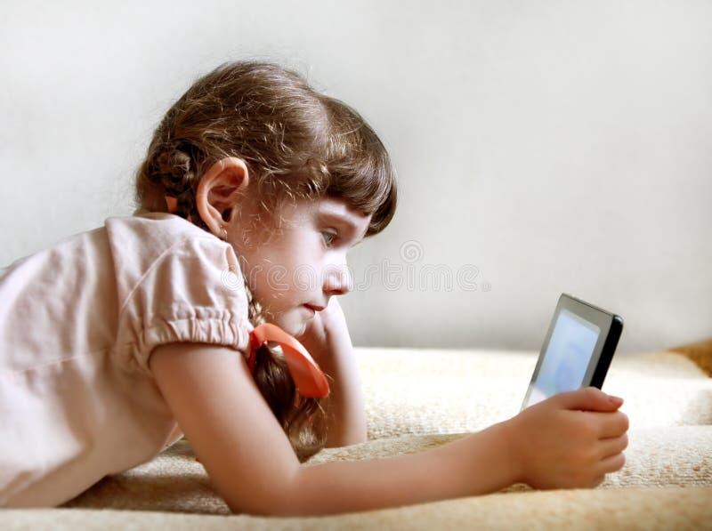 Liten flicka med tableten arkivbilder