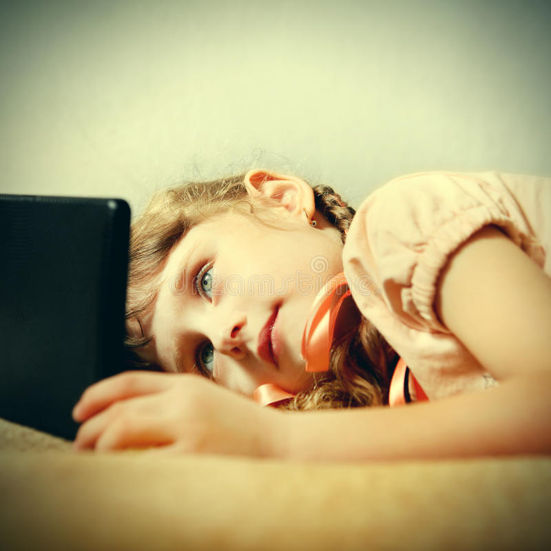 Liten flicka med tableten royaltyfria foton