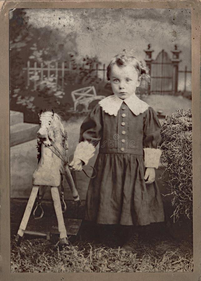 Liten flicka med Toy Horse royaltyfri foto