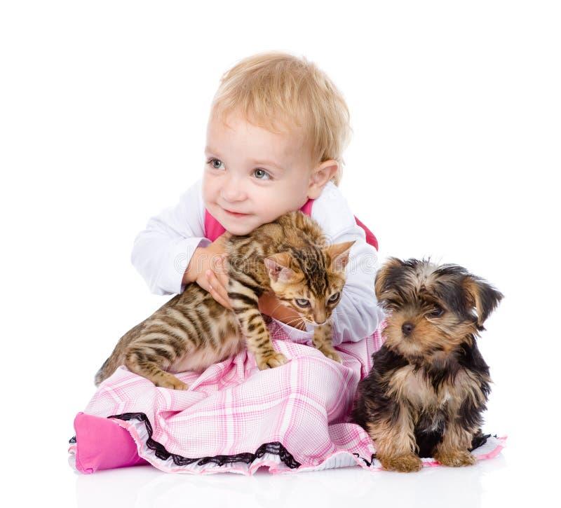 Liten flicka med valpen som kramar en kattunge Isolerat på vit backg arkivfoto