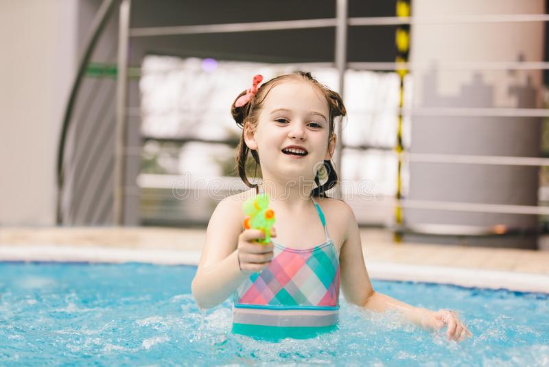 Liten flicka med vattenpistolen i en simbassäng arkivbilder