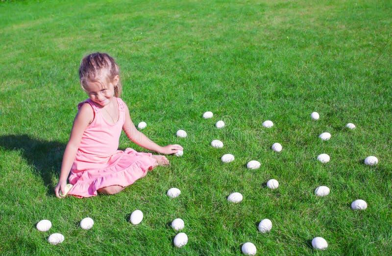 Liten flicka med vita påskägg i gården på royaltyfria foton