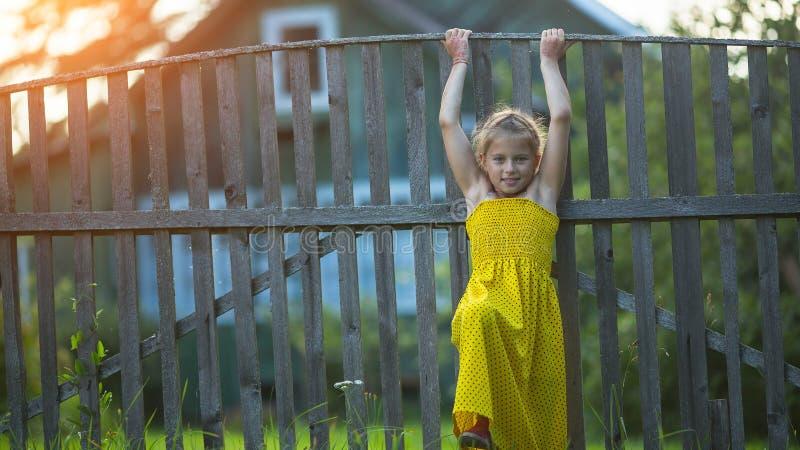 Liten flicka nära det wood staketet av ett byhus Lyckligt arkivbild