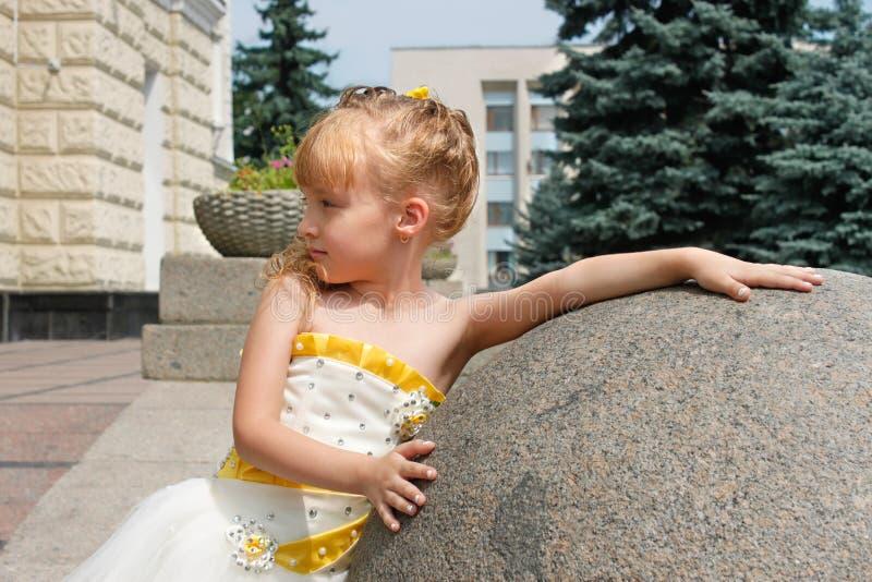 Liten flicka nära en marmorboll i en sommardag royaltyfri fotografi