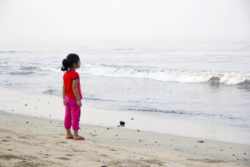 Liten flicka och att stå bara som ser havet, Alibag strand, Indien arkivbilder