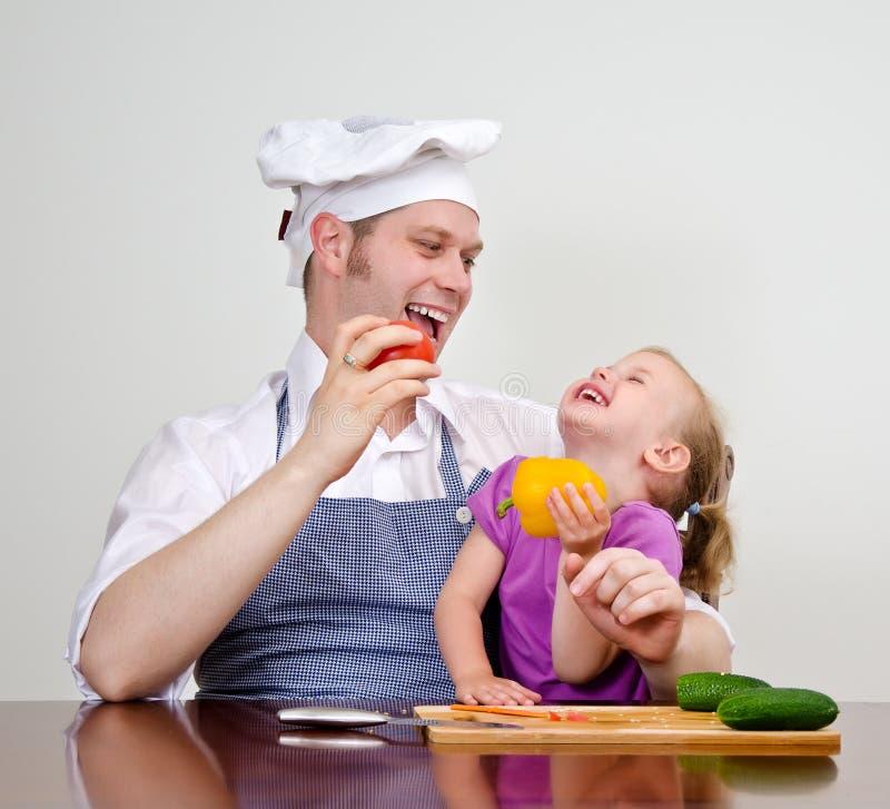 Liten flicka och fader i kök arkivfoton