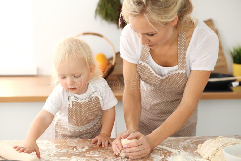 Liten flicka och hennes blonda mamma i beigea f?rkl?den som spelar och skrattar, medan kn?da degen i k?k hemlagad bakelse royaltyfria bilder