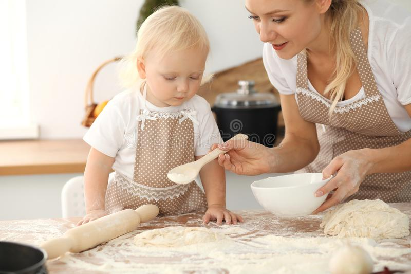 Liten flicka och hennes blonda mamma i beigea f?rkl?den som spelar och skrattar, medan kn?da degen i k?k hemlagad bakelse royaltyfri bild