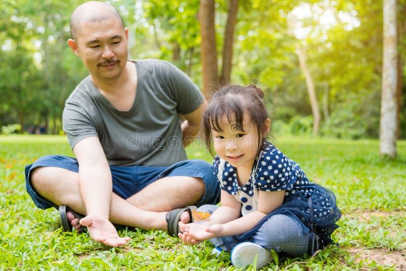 Liten flicka och hennes fader som ser fjärilar royaltyfri bild
