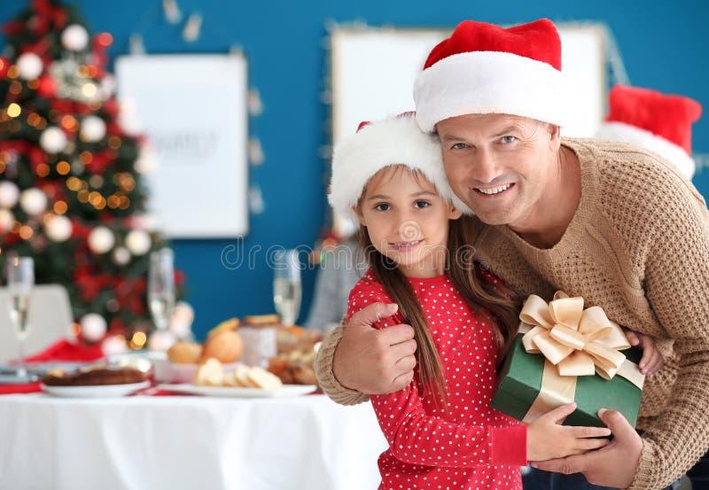 Liten flicka och hennes farfar med julgåvan hemma arkivfoton