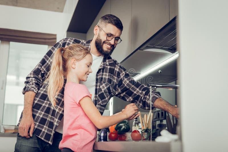 Liten flicka och hennes högväxta skäggiga fader i glasögon som spenderar tid i köket arkivbild