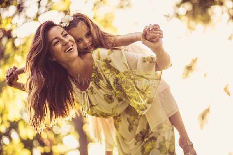 Liten flicka och hennes mamma som spelar på naturen royaltyfri fotografi