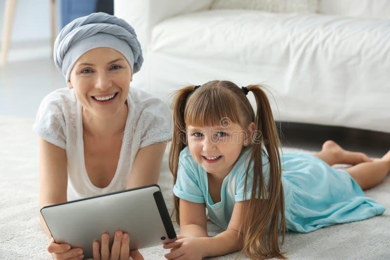 Liten flicka och hennes moder efter kemoterapi genom att använda minnestavlaPC hemma royaltyfri fotografi