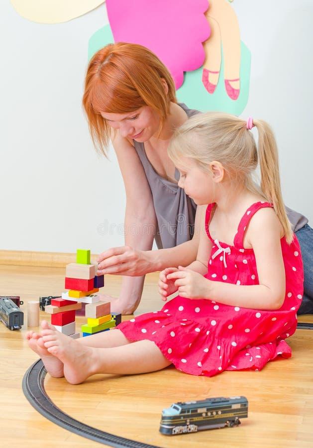 Liten flicka och hennes moder som spelar med järnvägen royaltyfria bilder