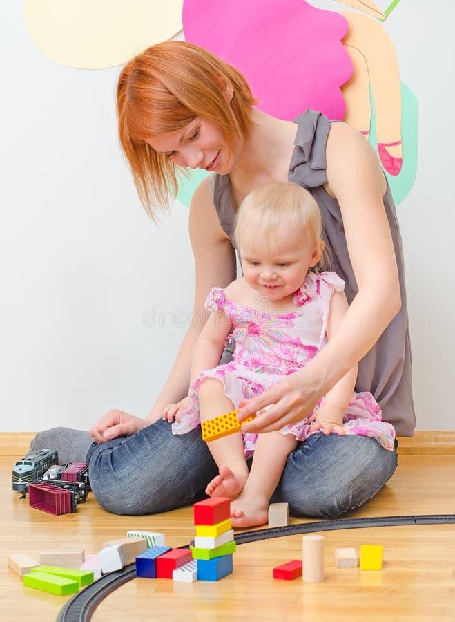 Liten flicka och hennes moder som spelar med järnvägen fotografering för bildbyråer