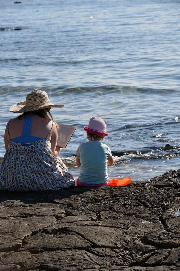 Liten flicka och hennes moder som spelar på stranden och läser en bok royaltyfri foto