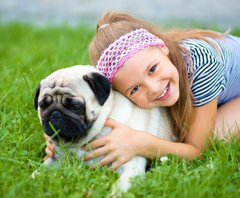 Liten flicka och hennes mopshund på grönt gräs royaltyfri bild