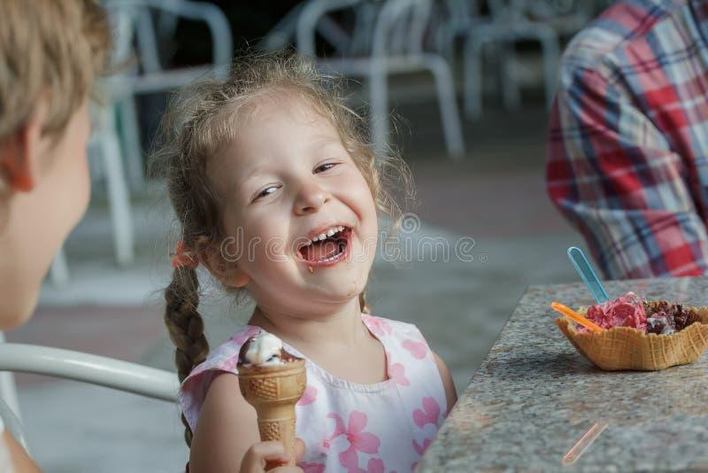 Liten flicka och hennes siblingbroder som skrattar under att äta italiensk glass royaltyfri fotografi