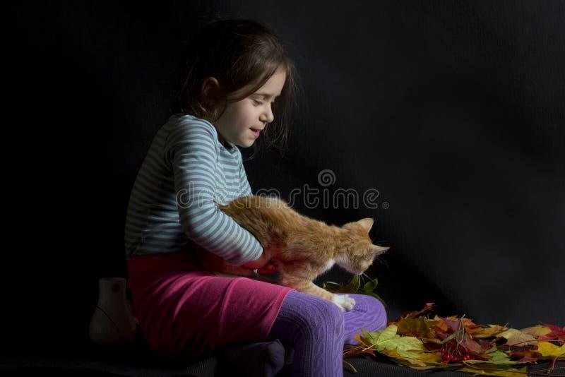 Liten flicka- och ingefärakattunge arkivfoto