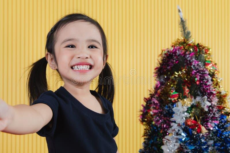 Liten flicka- och jultree royaltyfria foton