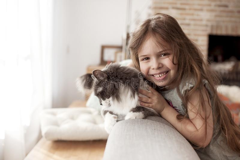 Liten flicka och katt hemma på soffan Ett lyckligt barn och ett husdjur kopiera avstånd arkivbild