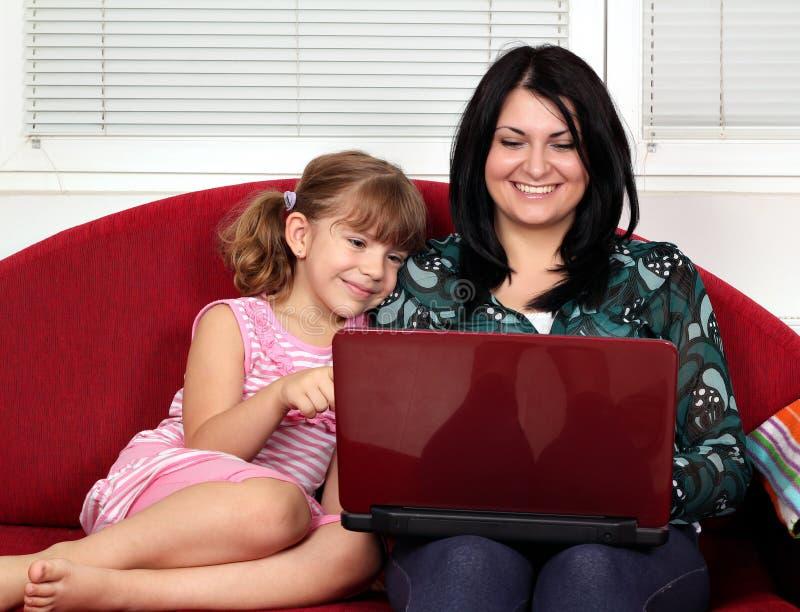 Liten flicka och kvinna med bärbara datorn royaltyfria foton