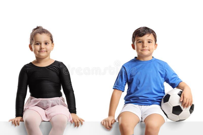 Liten flicka och lite fotbollsspelare för ballerina som sitter på en panel och ser kameran royaltyfria bilder