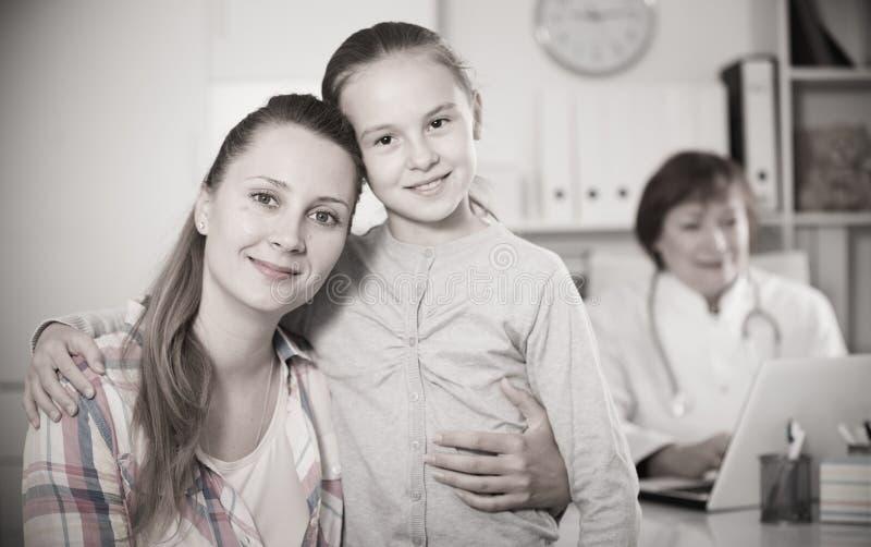 Liten flicka och moder med den mogna medicinska arbetaren arkivbild