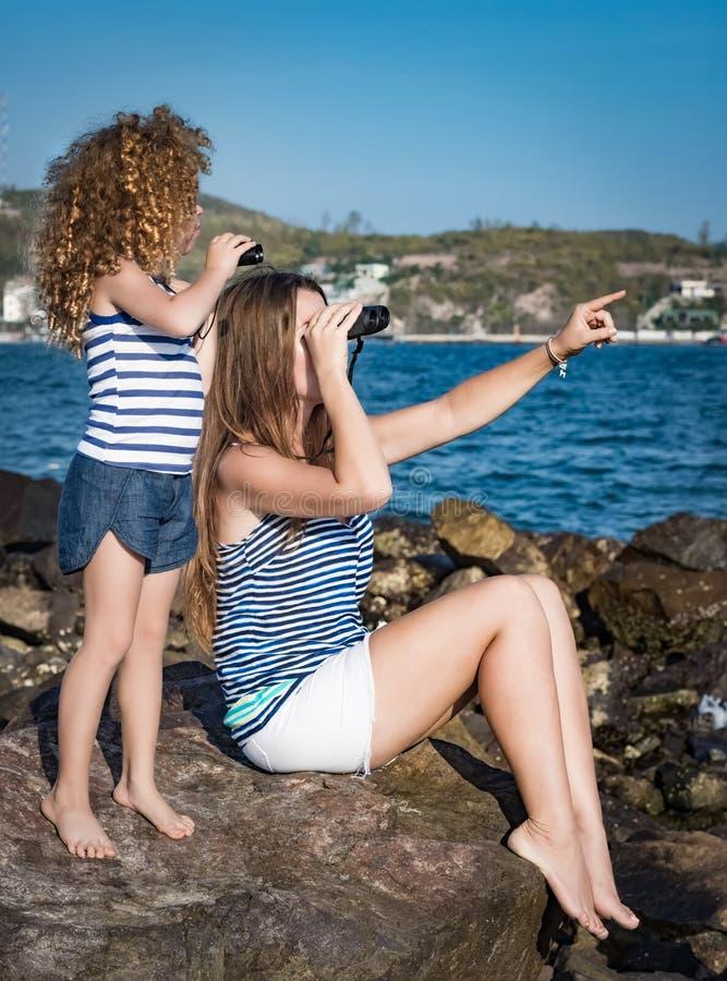 Liten flicka och moder som långt borta ser med kikare fotografering för bildbyråer