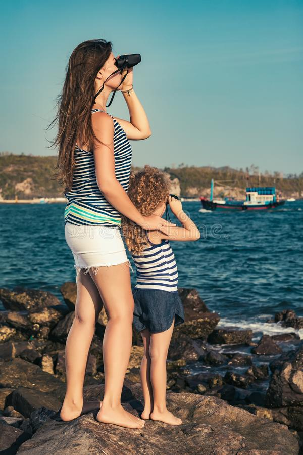 Liten flicka och moder som långt borta ser med kikare royaltyfri foto