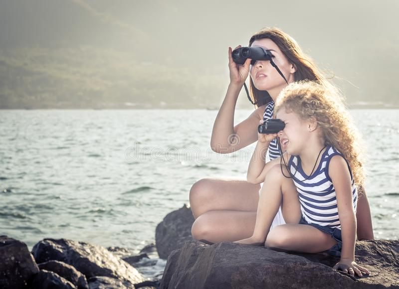 Liten flicka och moder som långt borta ser med kikare arkivfoto