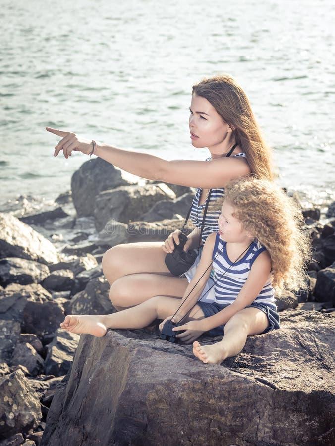Liten flicka och moder som långt borta ser med kikare royaltyfria bilder