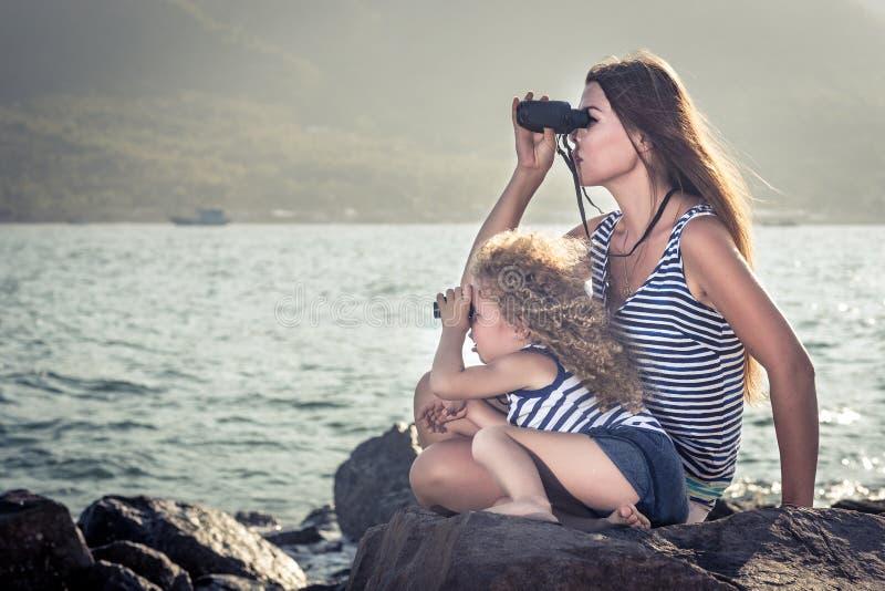 Liten flicka och moder som långt borta ser med kikare arkivfoton