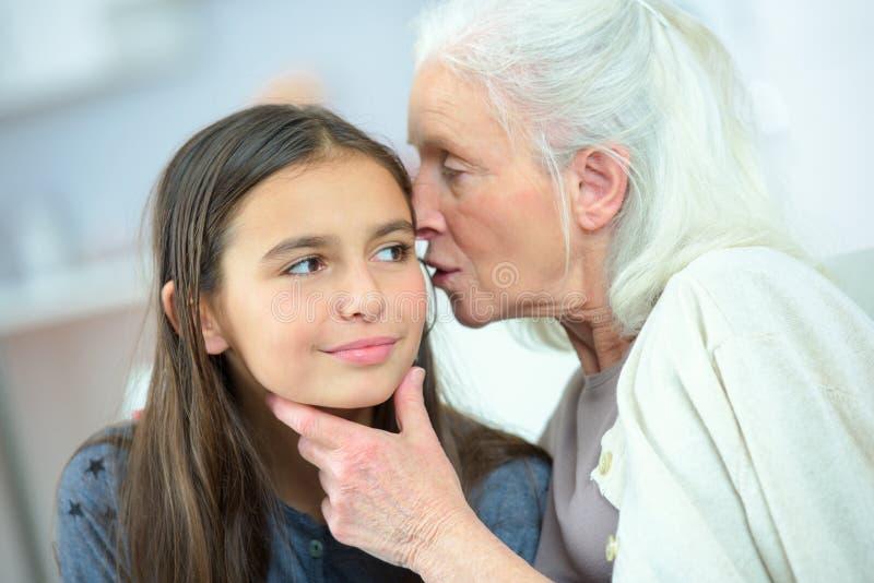 Liten flicka och mormor som viskar hemligheter arkivbild