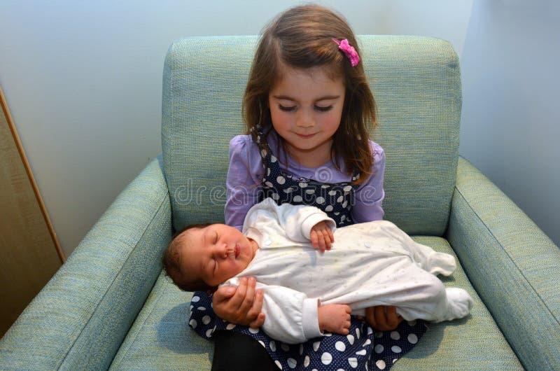 Liten flicka och nyfödd syster royaltyfri fotografi